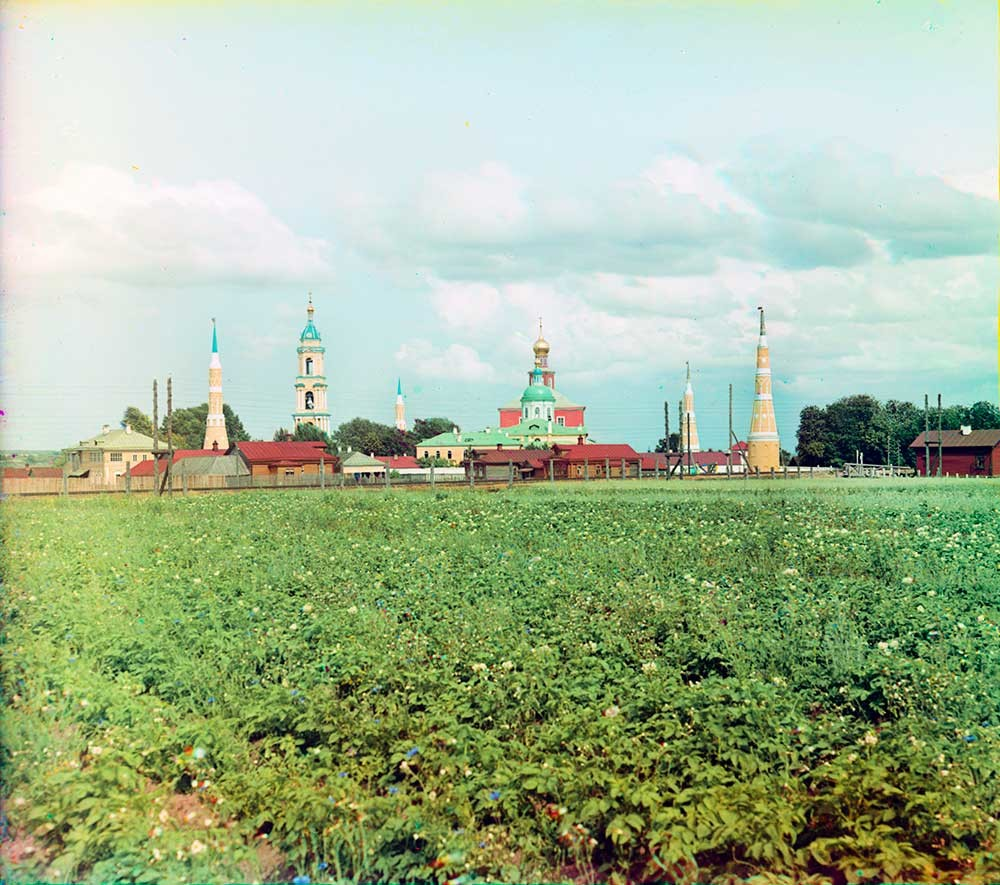 Old Golutvin Epiphany Monastery, west view. From left: northwest corner tower, bell tower, NE corner tower, Epiphany Cathedral & St. Sergius Church, SE corner tower, SW corner tower. Foreground: railroad & potato field. Summer 1912.