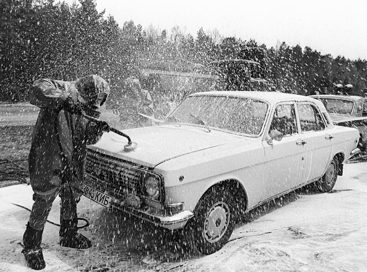 Dekontaminasi sebuah mobil yang keluar dari wilayah bencana.