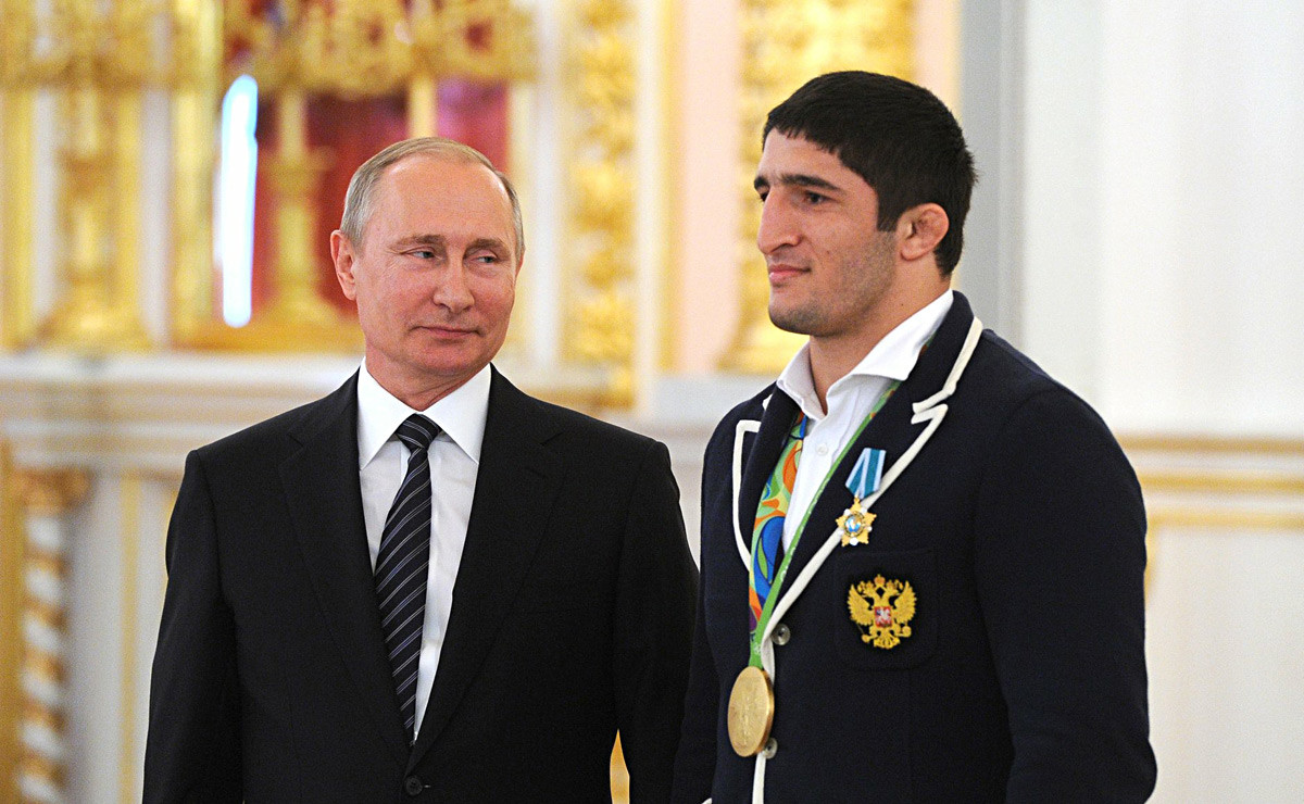 Presiden Rusia Vladimir Putin (kiri) dan juara gulat gaya bebas Olimpiade Rio 2016 Abdulrashid Sadulaev pada upacara upacara penyerahan penghargaan negara untuk Abdulrashid.