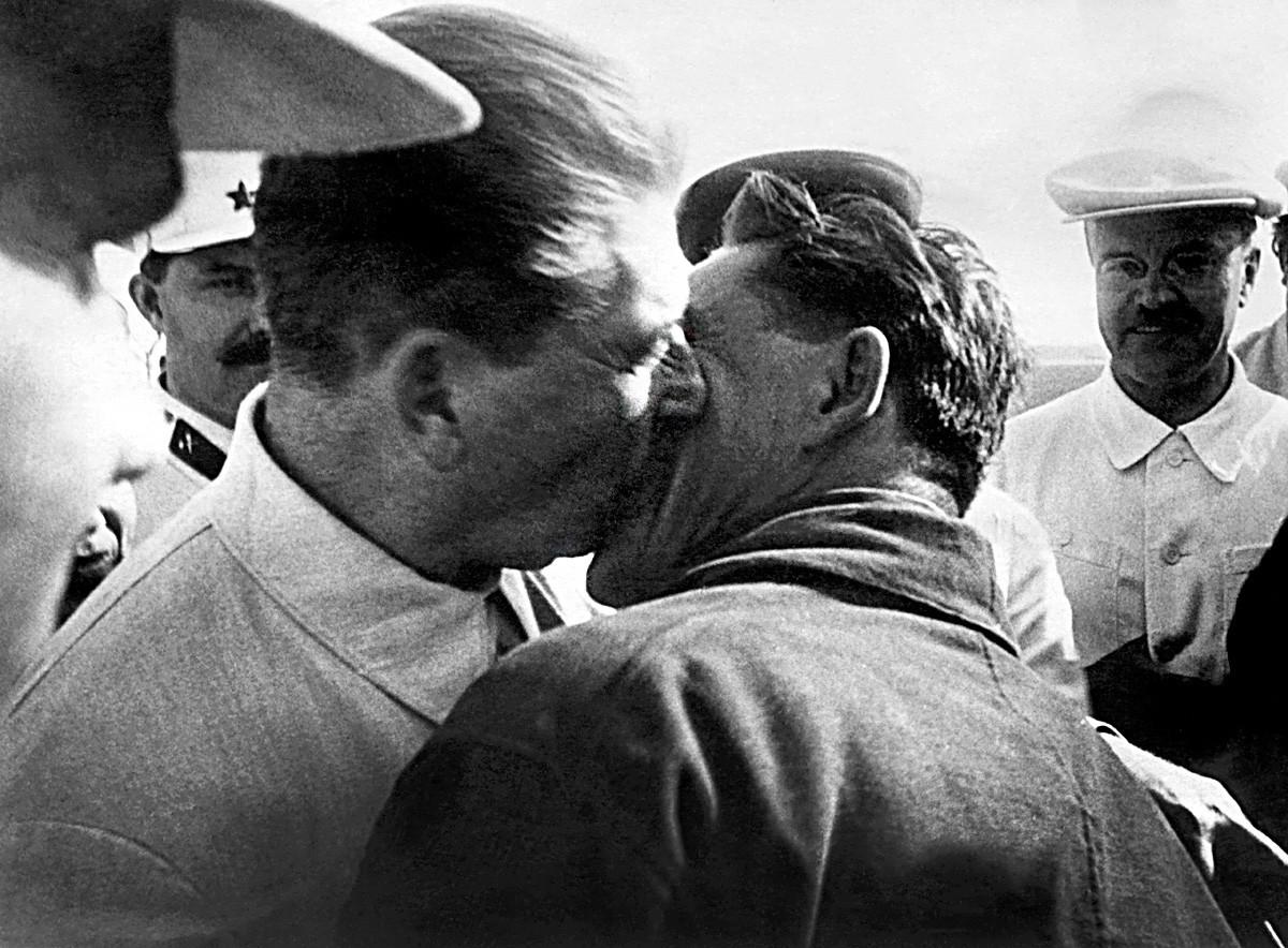 Joseph Stalin (kiri) mencium pilot Polar Vasily Molokov (kanan) sekembalinya di Moskow bersama Otto Schmidt (tidak digambarkan) penjelajah Kutub Utara pada 4 Juli 1937.