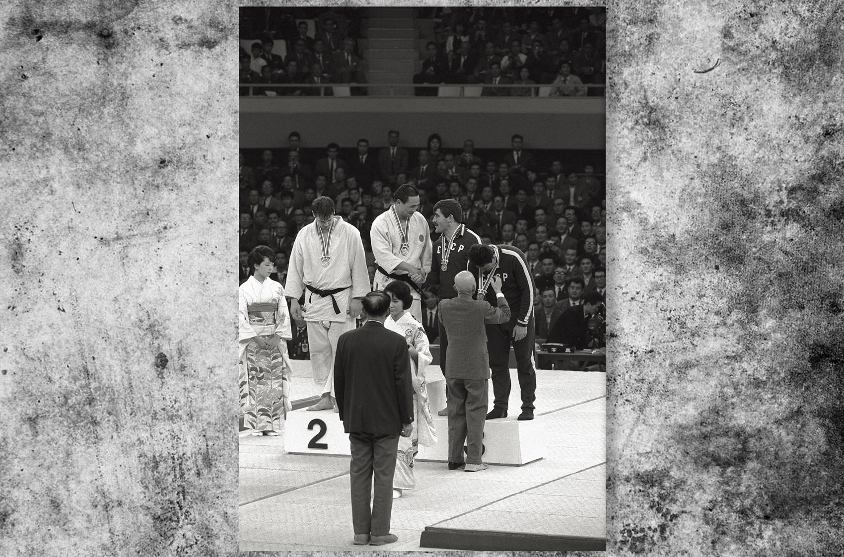 日本の柔道家、猪熊功が最重量級のメダルを受け取る。そばにはカナダのダグ・ロジャース選手、ソ連のパルナオズ・チクヴィラゼ選手とアンゾル・キクナゼ選手が立っている。東京オリンピック、1964年。