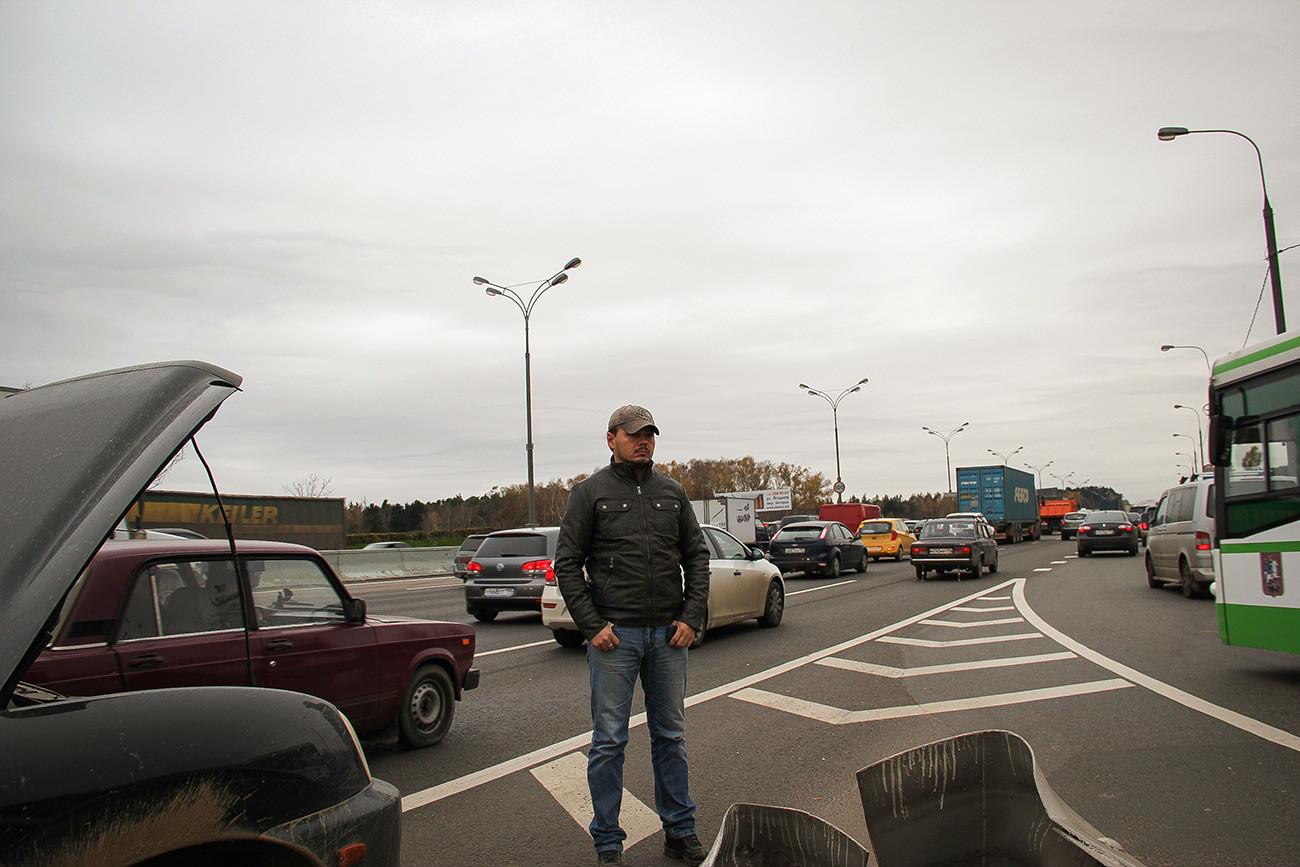 """Дмитриј, """"Санта из Бутова"""", стоји поред свог аута Hyundai Santa Fe и """"брани"""" траку за аутобусе."""