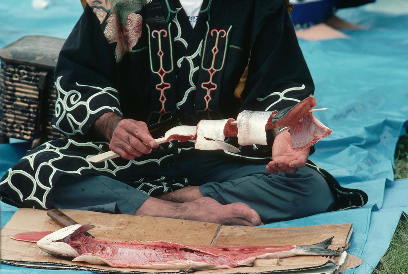 Представник народа Аину припрема лососа на Првом фестивалу лососа.