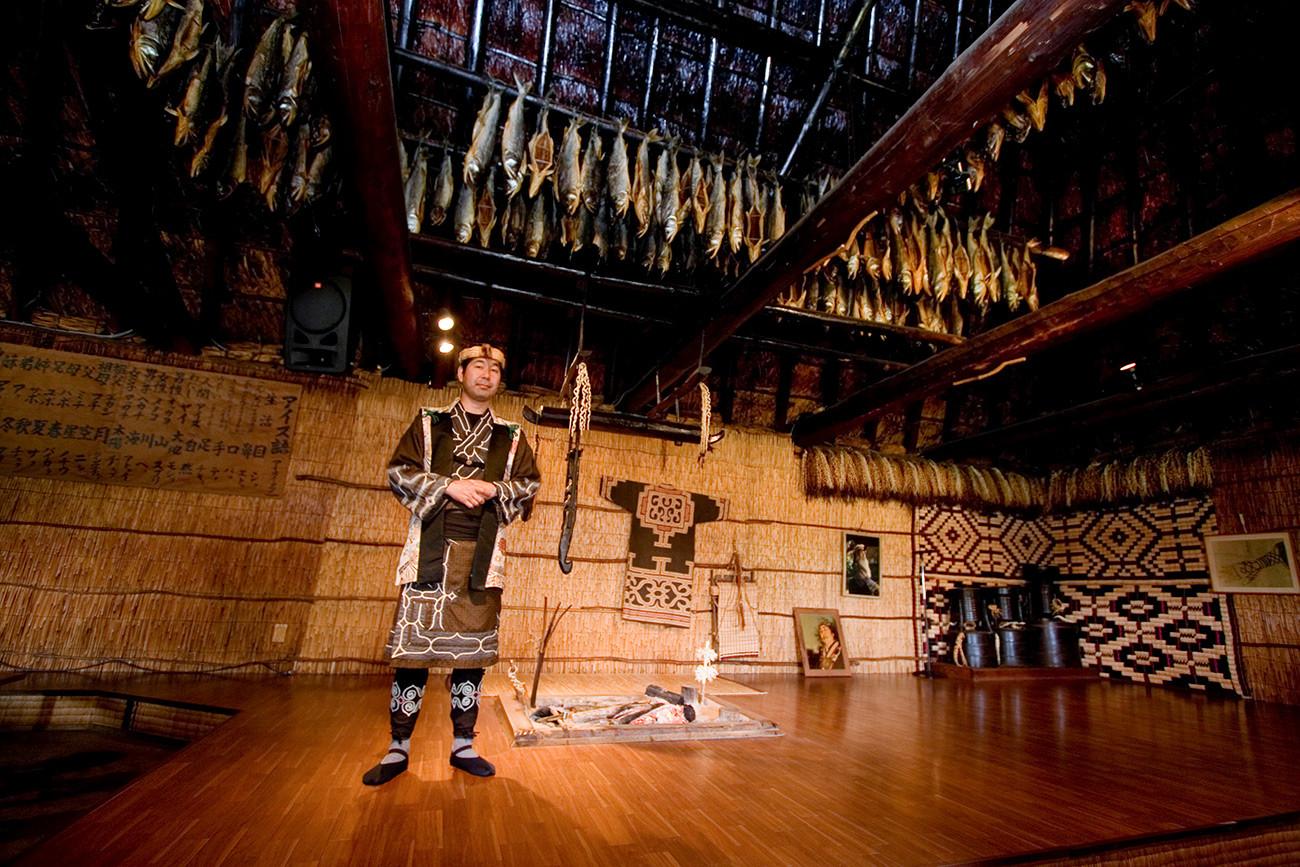 Човек из народа Аину испод таванице на којој се суши риба.