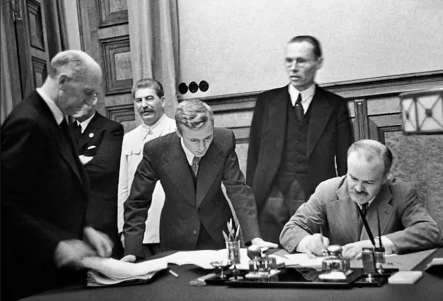 Le commissaire du peuple des affaires étrangères de l'URSS Viatcheslav Molotov signe un traité portant sur l'amitié et les frontières entre l'URSS et l'Allemagne. Parmi les personnes présentes : Staline, V. Pavlov, traducteur du ministère des Affaires étrangères.