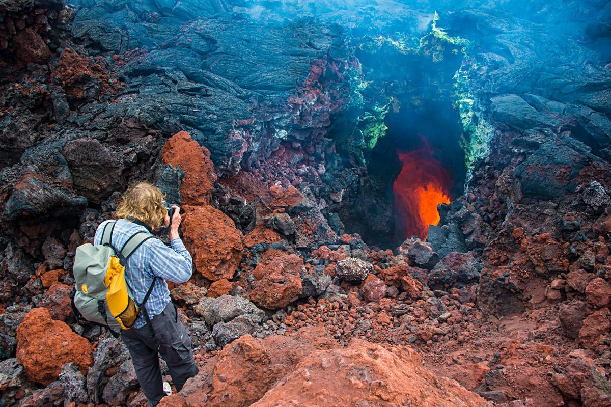Туриста фотографише усијану магму активног вулкана Толбачик, Камчатка, Русија.