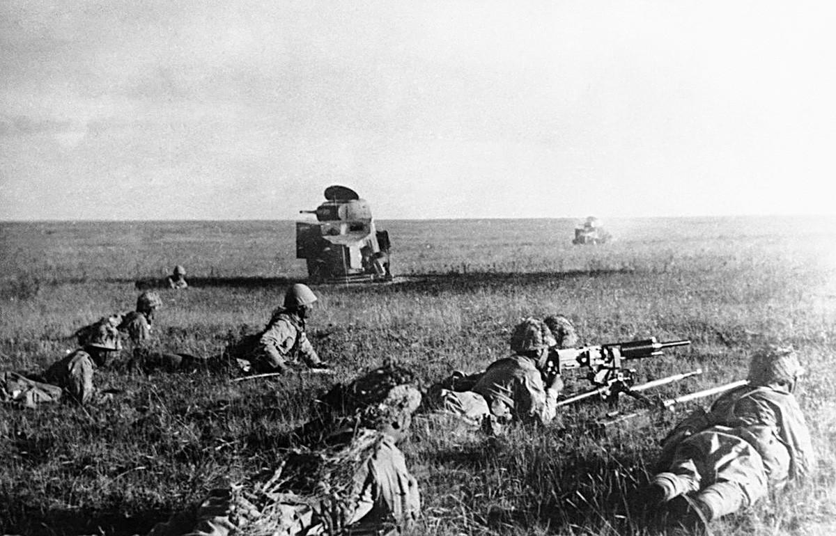Јапански војници пуцају из лежећег положаја испред уништених совјетских тенкова.