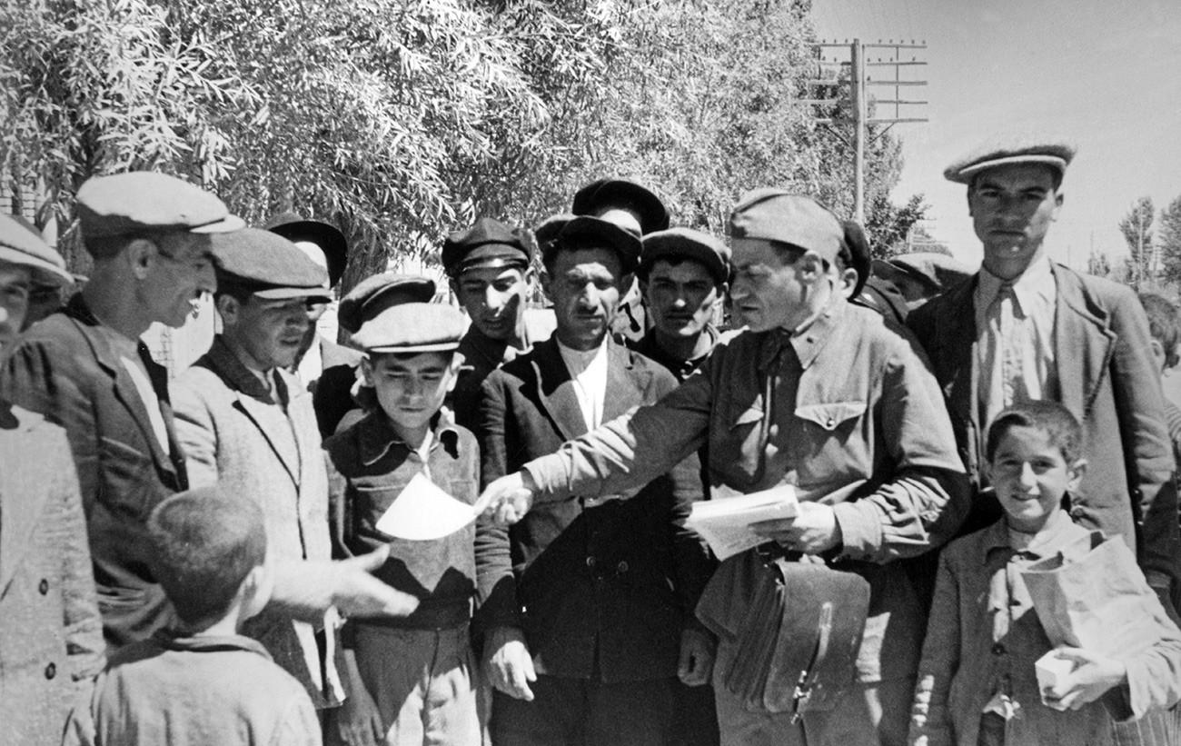 Советский военный политрук раздает жителям Тебриза пропагандистские листовки. Август 1941 года.