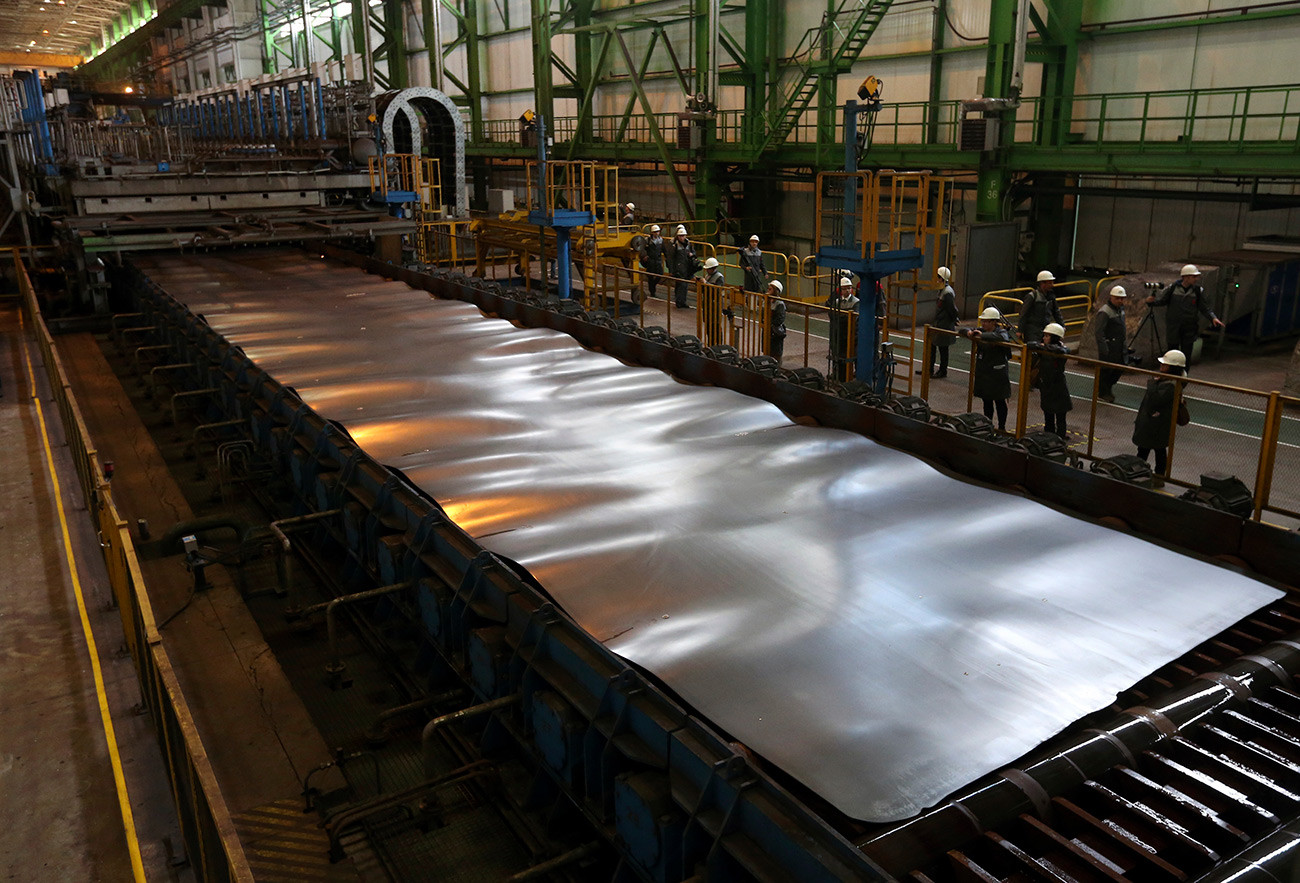 Employees stand near a metal sheet at the OMK metal works in Vyksa in the Nizhny Novgorod region.