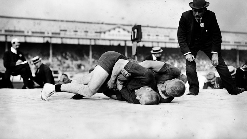 A referee watches the wrestling final at the 1908 London Olympics.