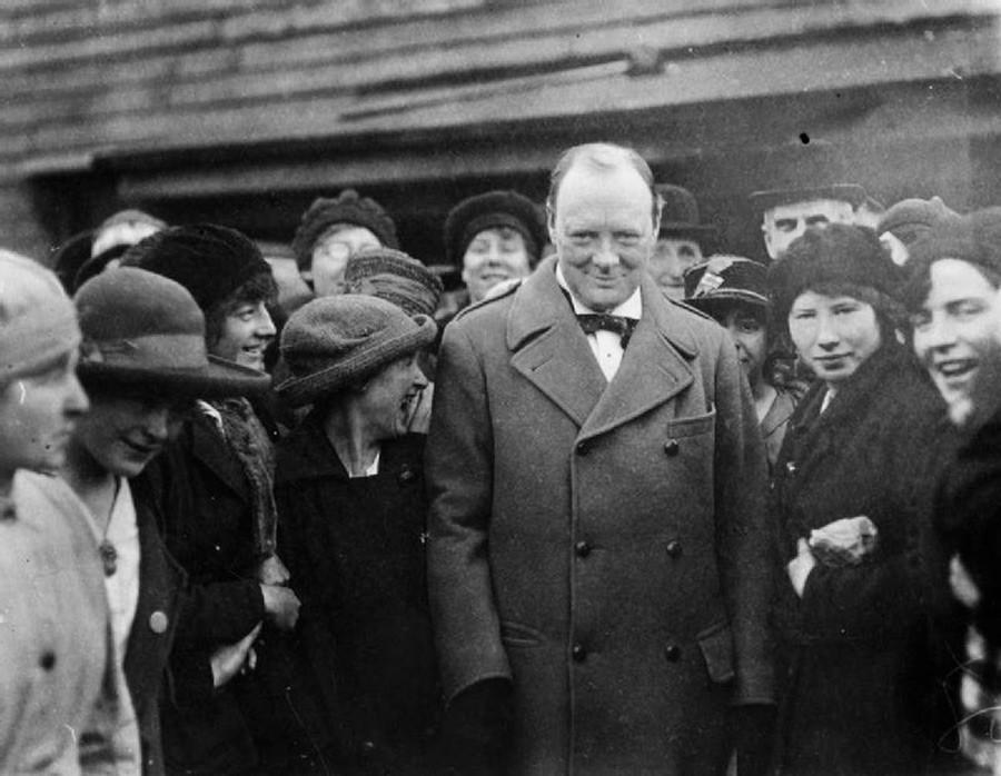 Le premier ministre Winston Churchill tire à l'aide d'une mitraillette Thompson Tommy aux côtés du commandant du Supreme Headquarters Allied Expeditionary Force, le général Dwight D. Eisenhower, sous le regard de soldats américains dans le Sud de l'Angleterre, fin mars 1944.