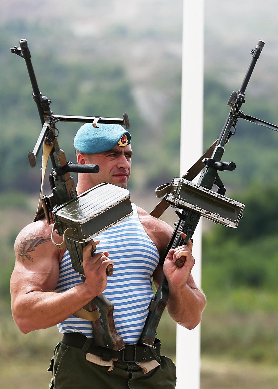 Seorang penerjun payung memegang senapan mesin saat pada pertunjukan militer dalam rangka memperingati Hari Pasukan Penerjun Paying di wilayah Krasnodar, Rusia.