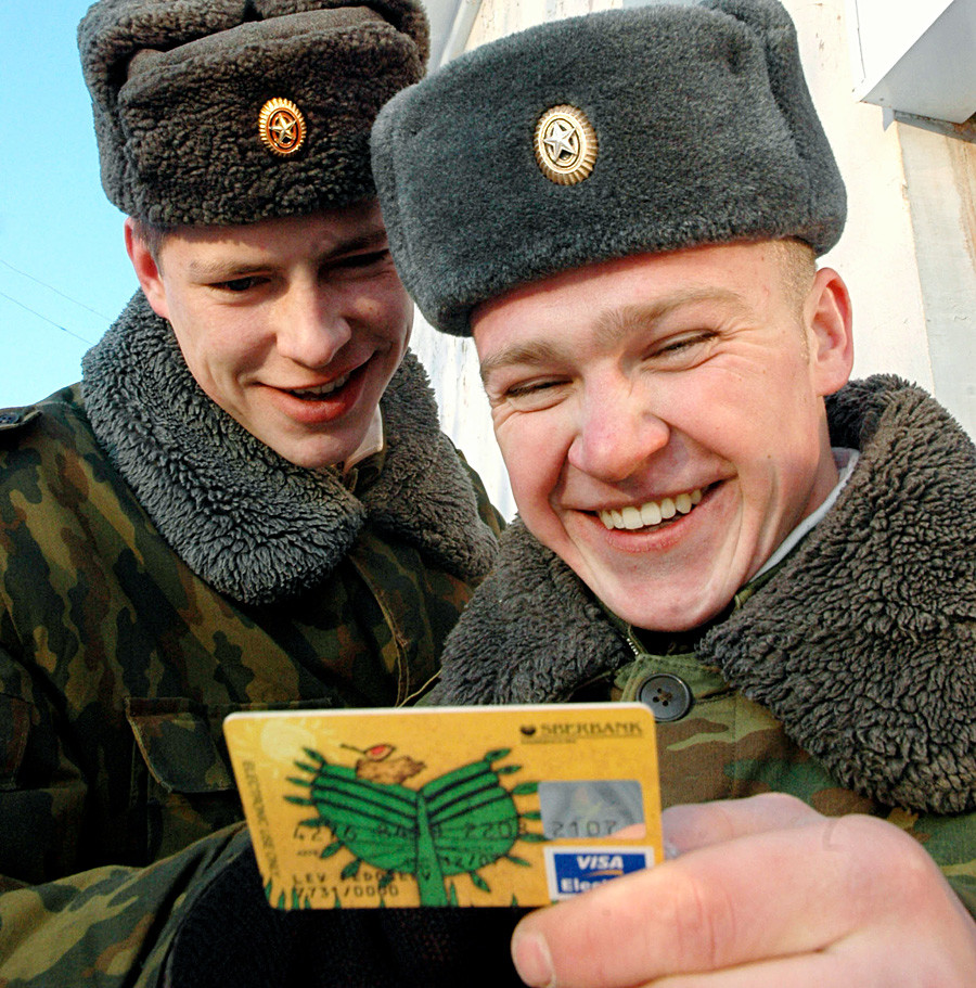 Tentara kontrak hendak menarik uang gaji dari mesin ATM.