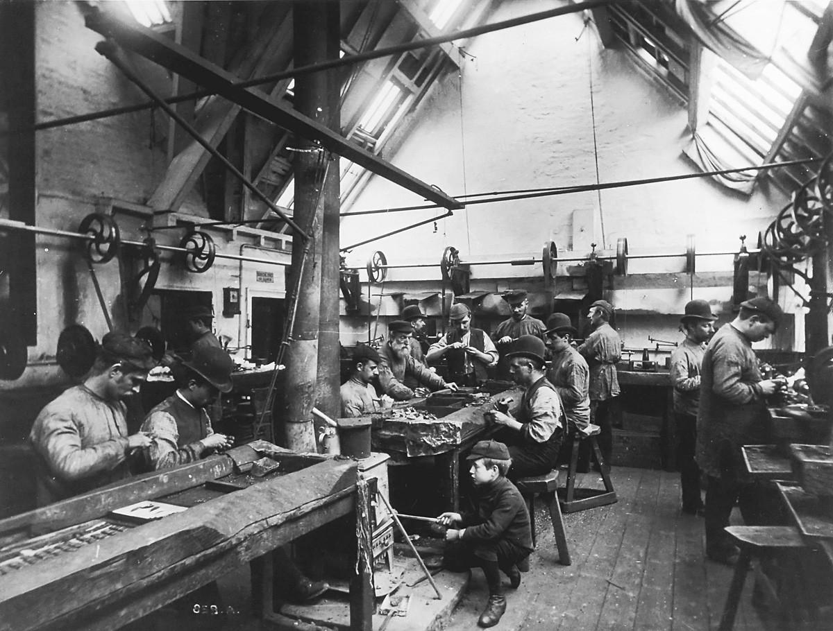 Immigrants, peut-être d'origine russe et d'Europe de l'Est, travaillant dans un atelier de métallurgie aux États-Unis. Un garçon allume un poêle à charbon.