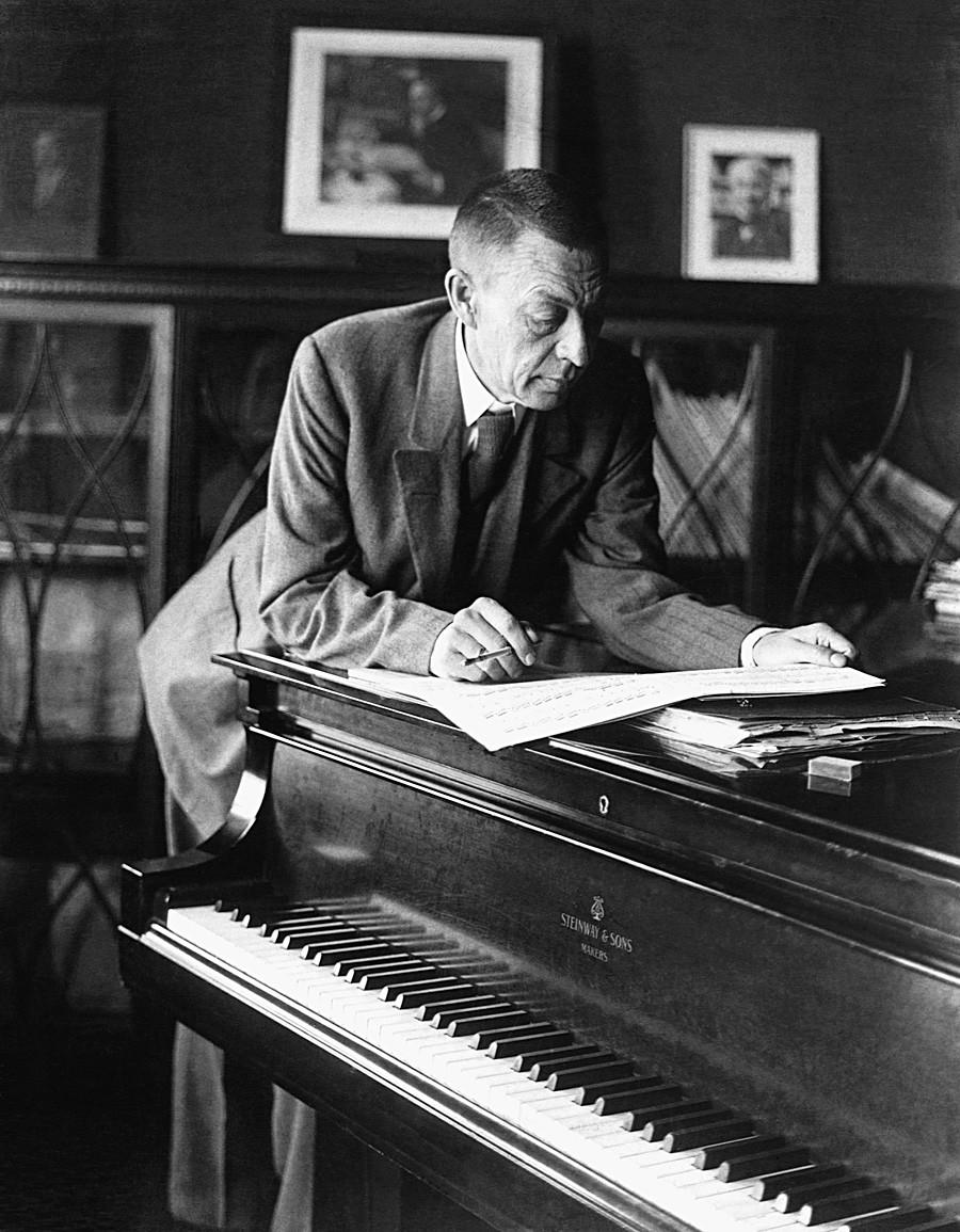 Le compositeur et pianiste d'origine russe Sergueï Rachmaninov (1873-1943) lit une partition musicale au-dessus d'un piano. Années 1920