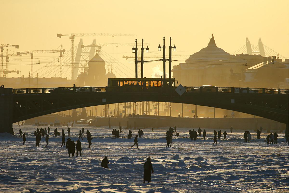 Začetek marca 2018, ljudje se sprehajajo po zmrznjeni reki Nevi v centru Sankt Peterburga