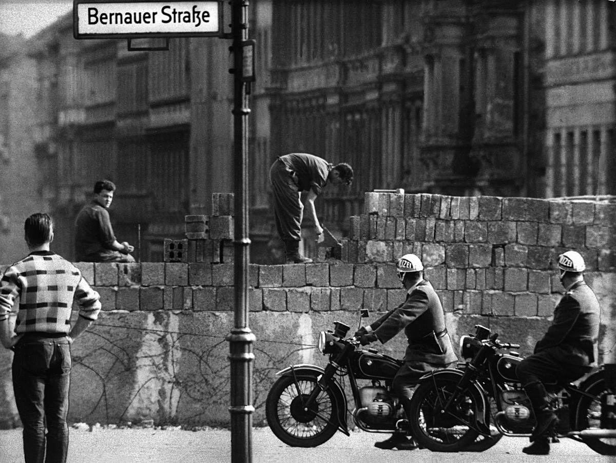 Police officers on a motorbike watch workers lay bricks on the other side of the so-called Berlin Wall in the street Bernauer Strasse in Berlin, Germany. On the morning of August 13, 1961,