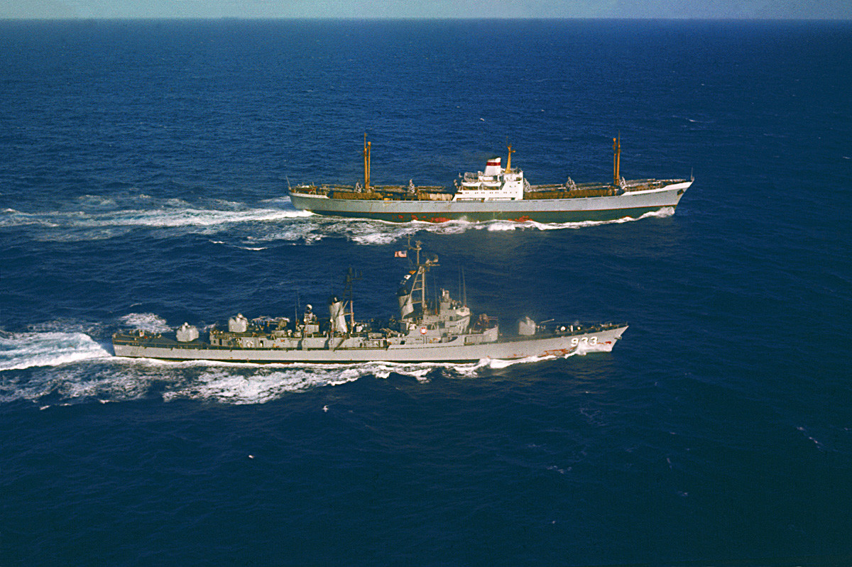 The USS Barry (left) steams alongside the Soviet freighter Ansov, outbound from Cuba, for an inspection of her cargo early today.