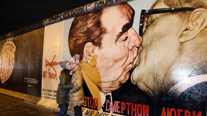 Dua orang wanita berpose di depan lukisan grafiti karya Dmitri Vrubel yang menggambarkan ciuman persaudaraan antara Pemimpin Soviet Leonid Brezhnev (kiri) dan Pemimpin Jerman Timur Erich Honecker di East Side Gallery, Berlin Wall art, Jerman.