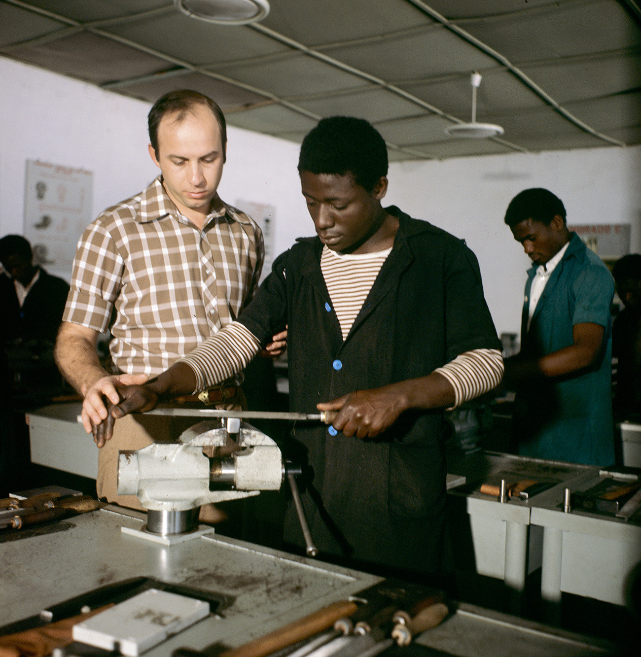 A Soviet locksmith teaching an African student.