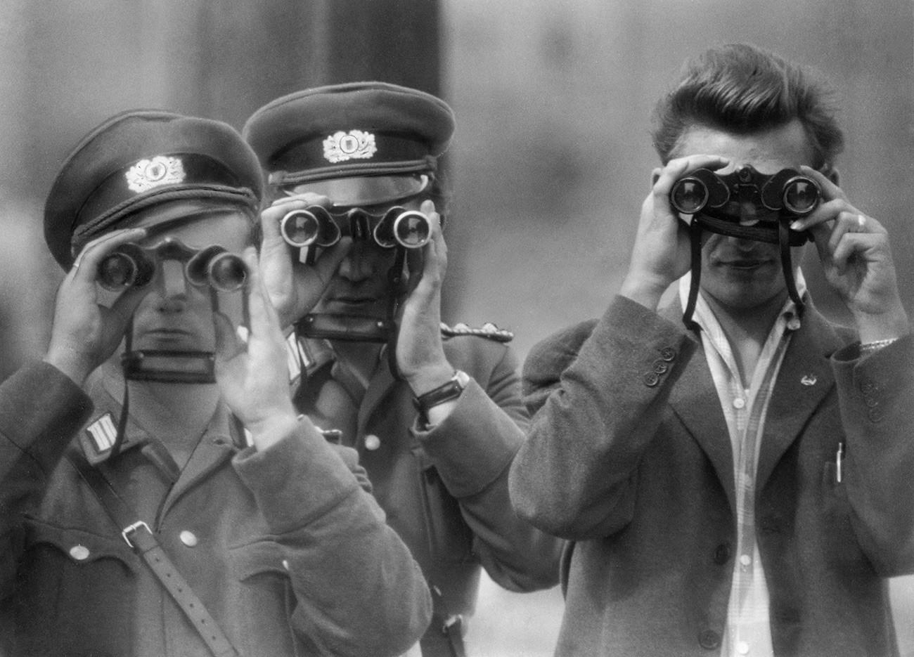 Due poliziotti della Germania dell'Est e un civile guardano con il binocolo la costruzione del Muro di Berlino