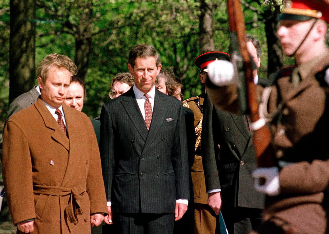 Владимир Путин (лево), кој тогаш бил задолжен за надворешните односи на Санкт Петербург кај градоначалникот Анатолиј Собчак, присуствува на церемонијата на полагање венци со принцот Чарлс на Пискарјовските гробишта во Санкт Петербург, Фотографијата е направена на 17 мај 1994 година.