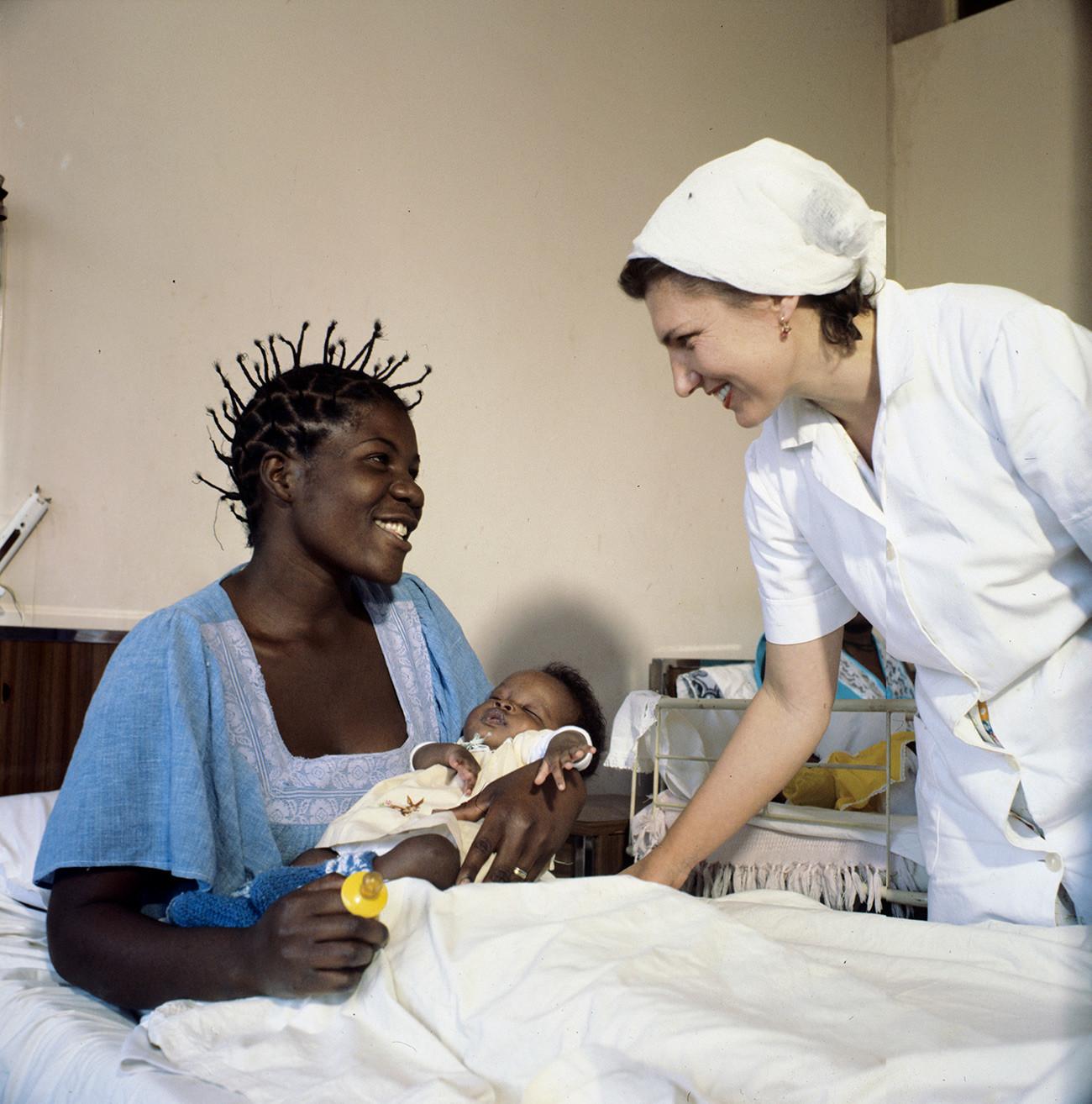 Bidan Soviet berbincang dengan seorang pasien di Lubango, Angola. Salah satu bentuk bantuan yang berikan Soviet kepada Afrika adalah tenaga medis.