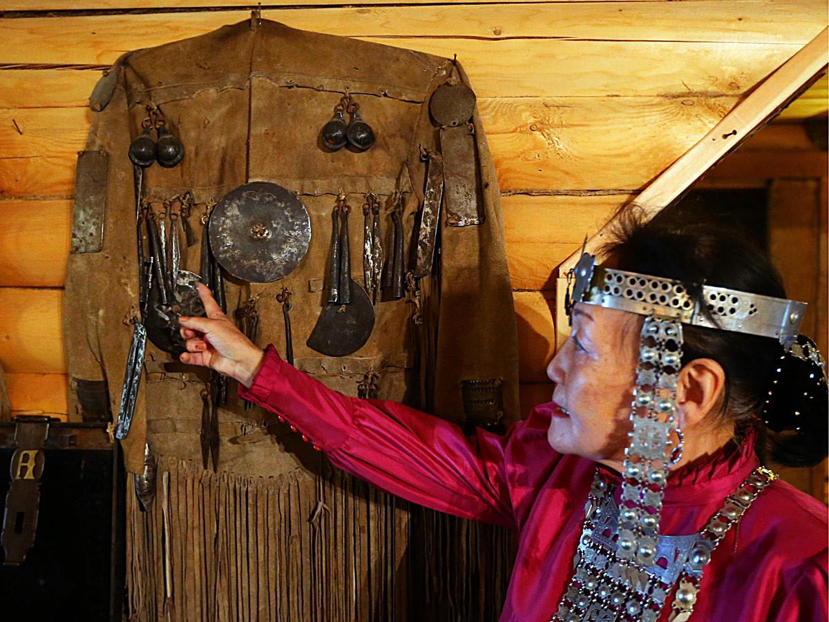 Valentina Atlasova, vestita con gli abiti tradizionali del luogo, mostra un costume da sciamano