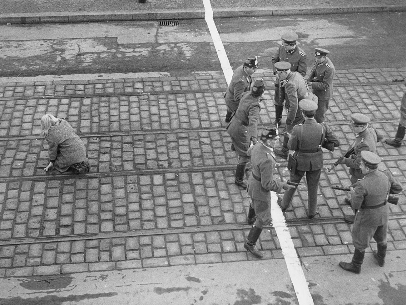 """Немачка глумица Нана Остен (лево) у улози Рите, другарице бегунца из Источне Немачке у сцени из филма """"Данас у Берлину"""" редитеља Пјера Виварелија, 1962. Са десне стране су глумци који играју западноберлинске полицајце и представнике источнонемачке народне полиције."""