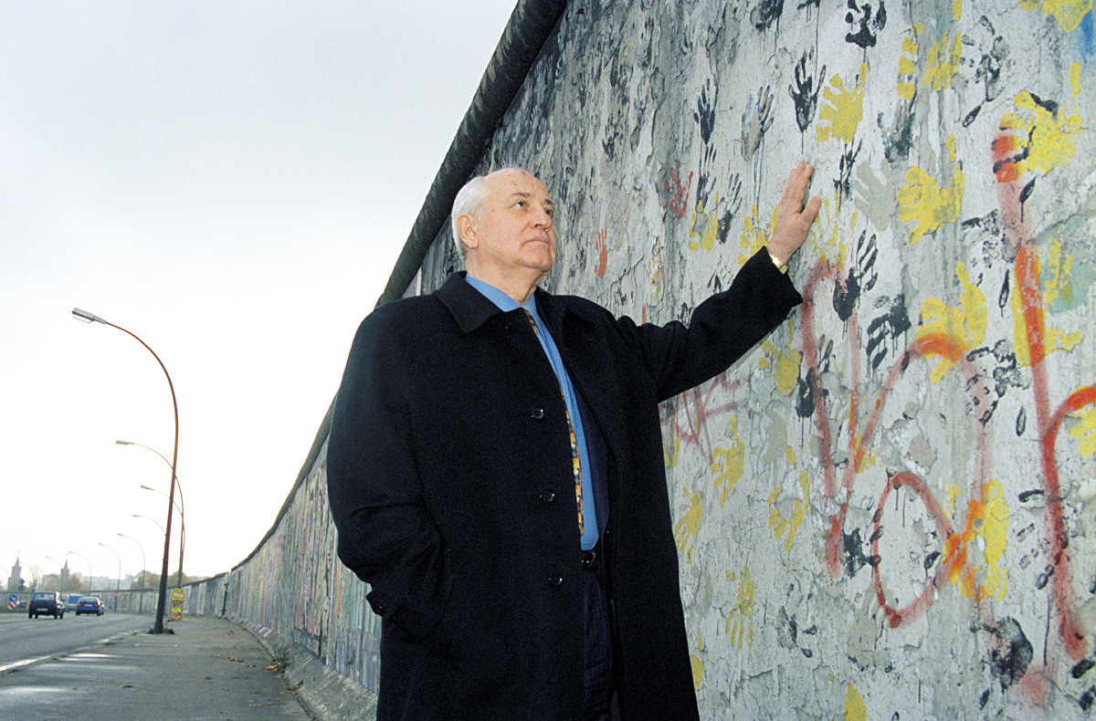 Mikhail Gorbachev, laureate of the 1990 Nobel Peace Prize, stands next to the Wall