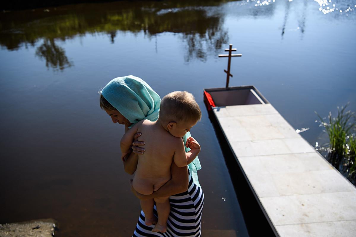 Seorang ibu dan anaknya di Sungai Chusovaya selama upacara pembaptisan massal Katedral Pangeran Vladimir di Desa Stantsionny-Polevskoi pada Hari Kristenisasi Rus.