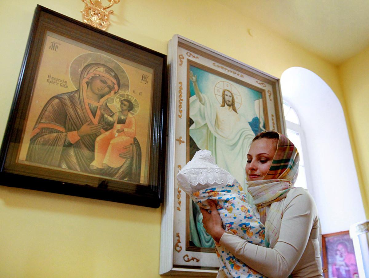 Seorang perempuan menggendong anaknya saat upacara pembaptisan bayi di Gereja Svyatitelya Nikolaya, Vladivostok.