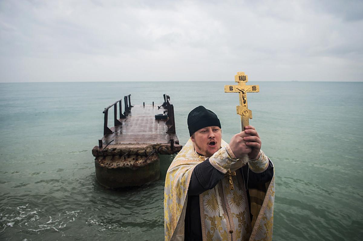Seorang pendeta memimpin upacara pemberkatan air di Laut Hitam, Distrik Khotinsky, Sochi.