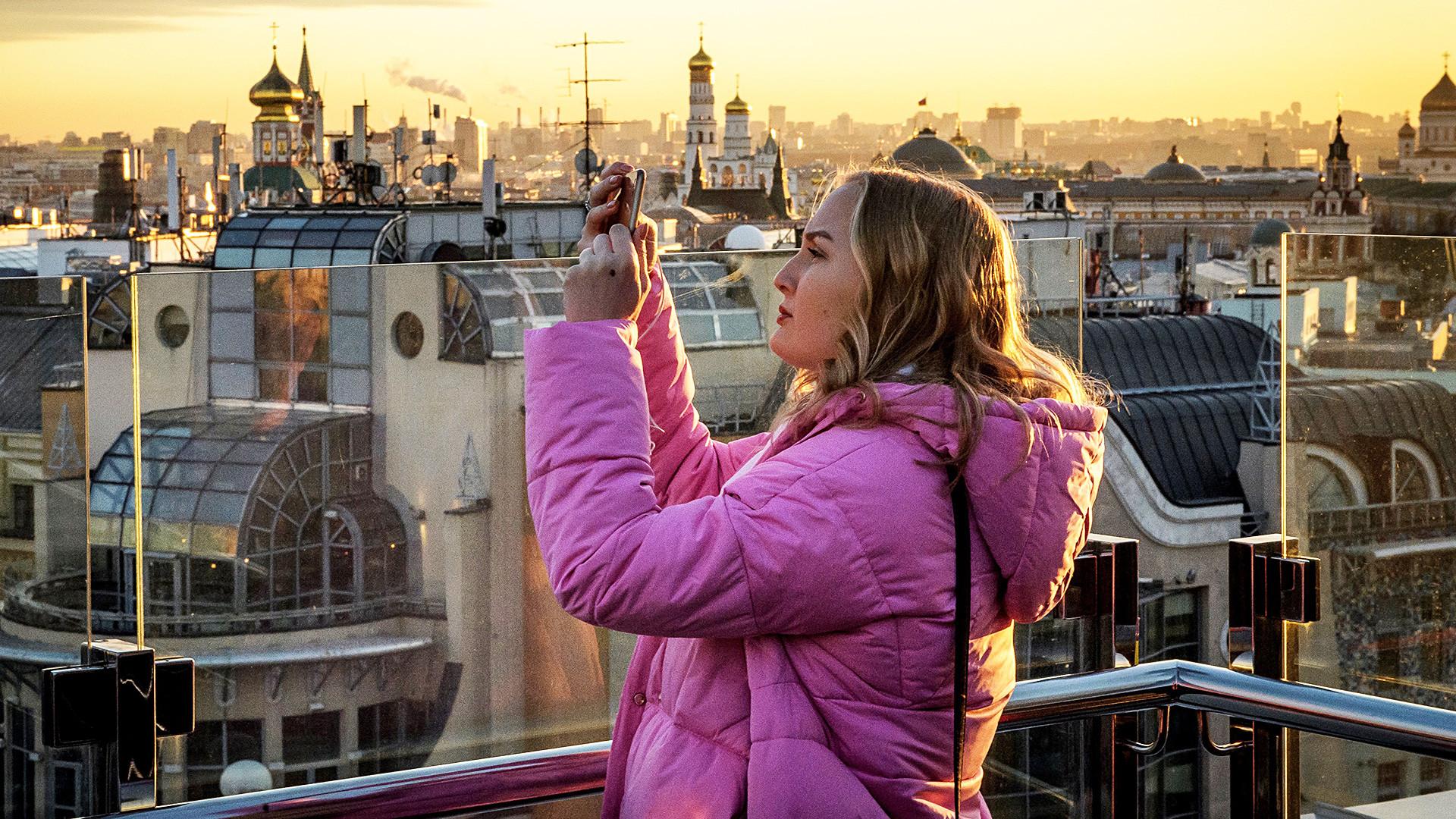 Touriste profitant du coucher de soleil depuis la plateforme d'observation au sommet du centre commercial pour enfants Detski Mir, à Moscou.