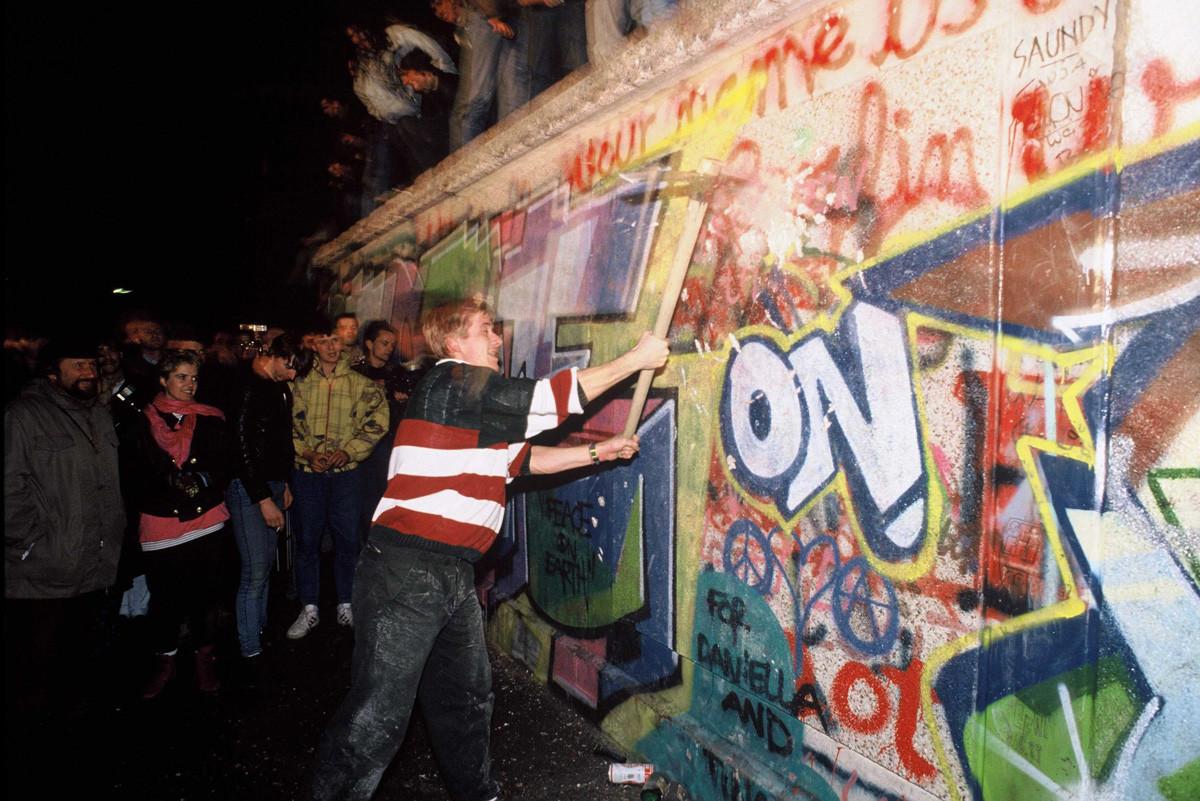 Демонстранты бросаются на стену с кувалдами.