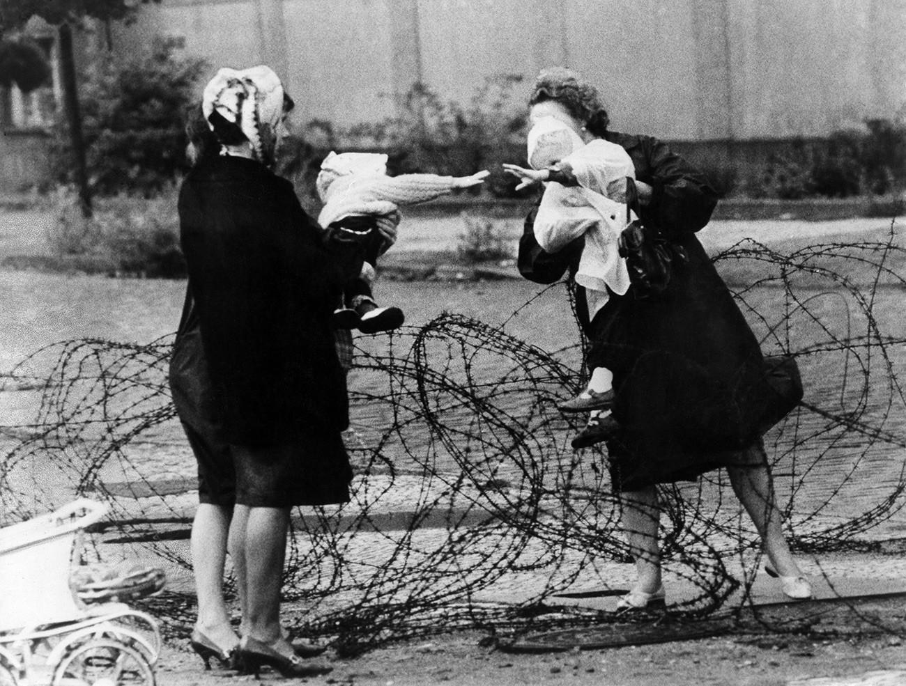 Ibu dengan anak dipisahkan oleh kawat berduri di Berlin, Agustus 1961.