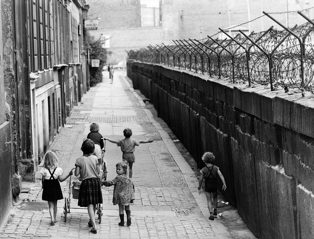 Anak-anak melintas di dekat Tembok Berlin di Sebastianstrasse, Berlin, Kreuzberg , sekitar 1964.