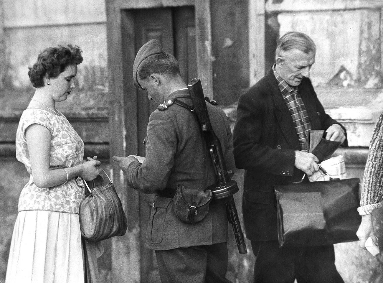 Orang-orang yang tinggal di dekat perbatasan dikontrol oleh polisi Jerman Timur (VOPO) sebelum memasuki flat mereka.