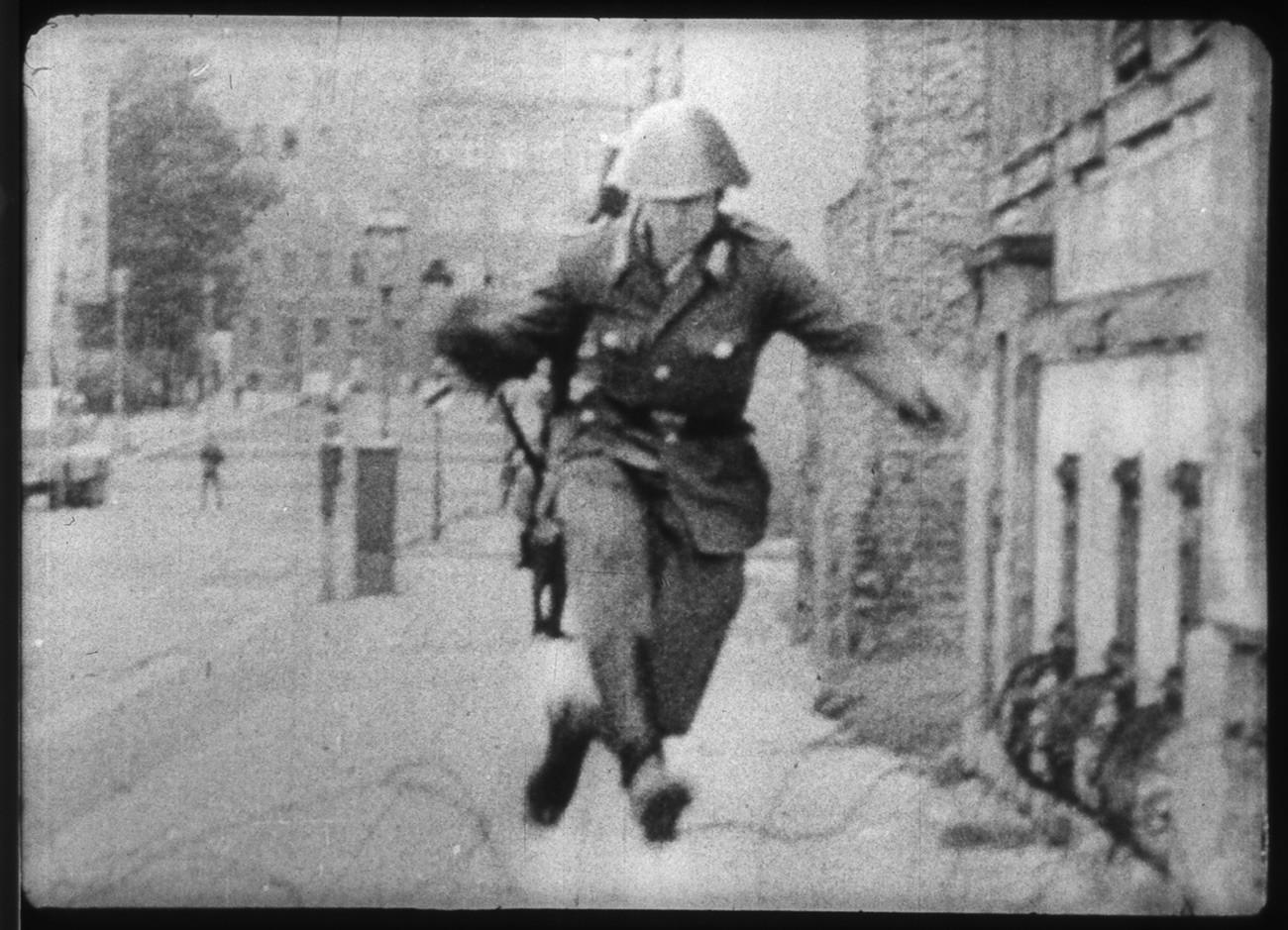 Tentara Penjaga Jerman Timur Conrad Schumann melompati kawat berduri ketika melarikan diri ke Berlin Barat.