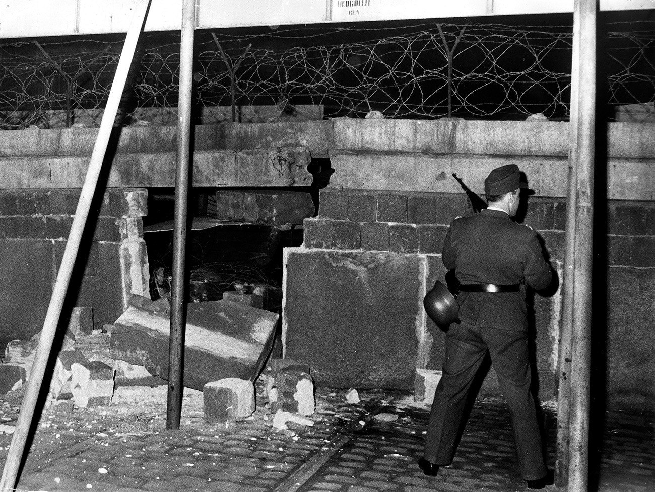 Polisi Jerman Timur menjaga tembok yang hancur ditabrak mobil pengangkut personel lapis baja yang dikendarai Wolfgang Engels dalam upaya pelarian dirinya ke Barat.
