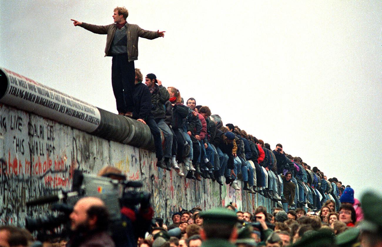 Orang-orang bertengger di Tembok Berlin.
