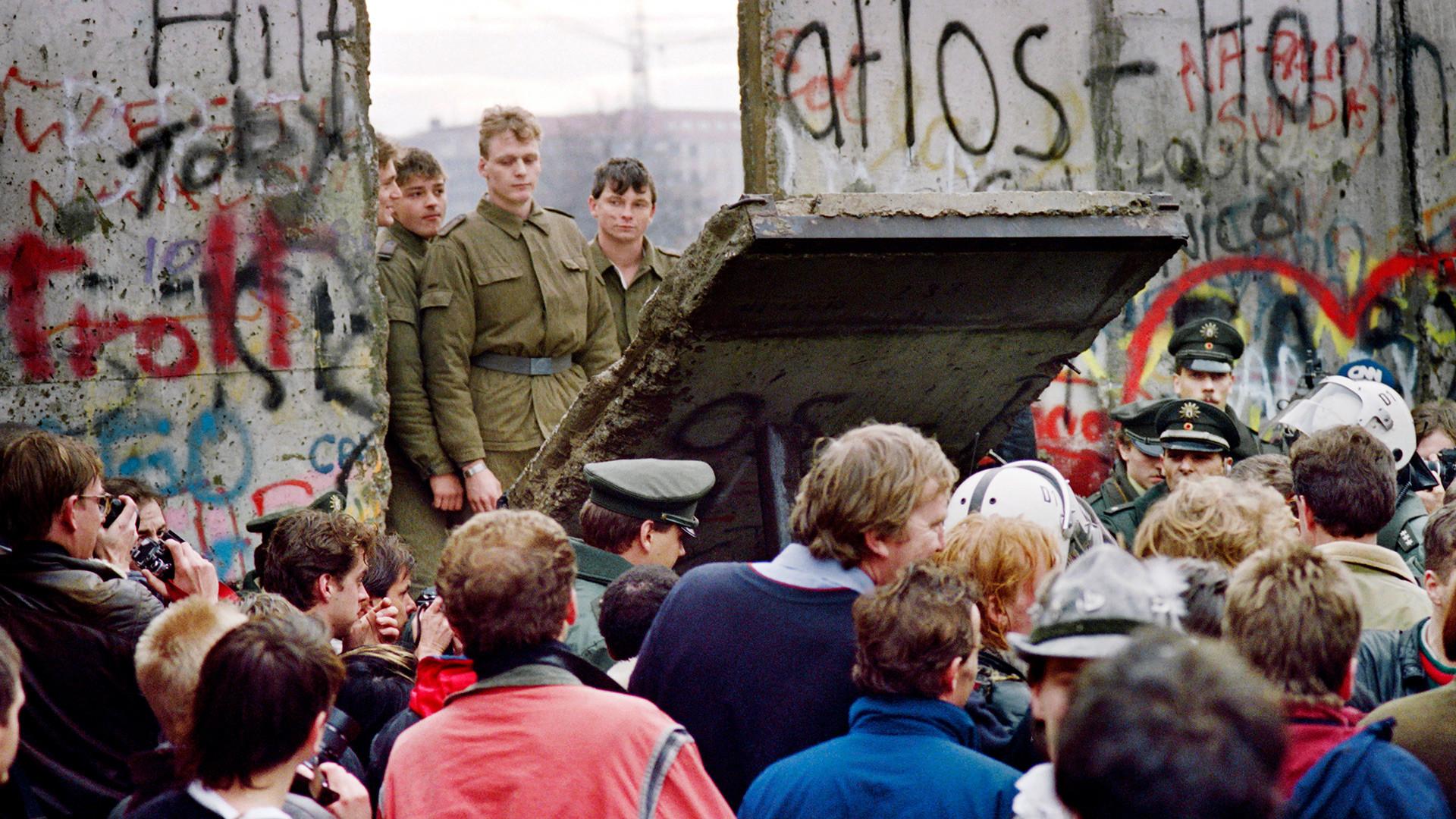 Warga Berlin Barat berkerumun di depan Tembok Berlin ketika menyaksikan penjaga perbatasan Jerman Timur menghancurkan bagian dinding untuk membuka titik persimpangan baru antara Berlin Timur dan Barat, di dekat Potsdamer Square,  awal 11 November 1989 .