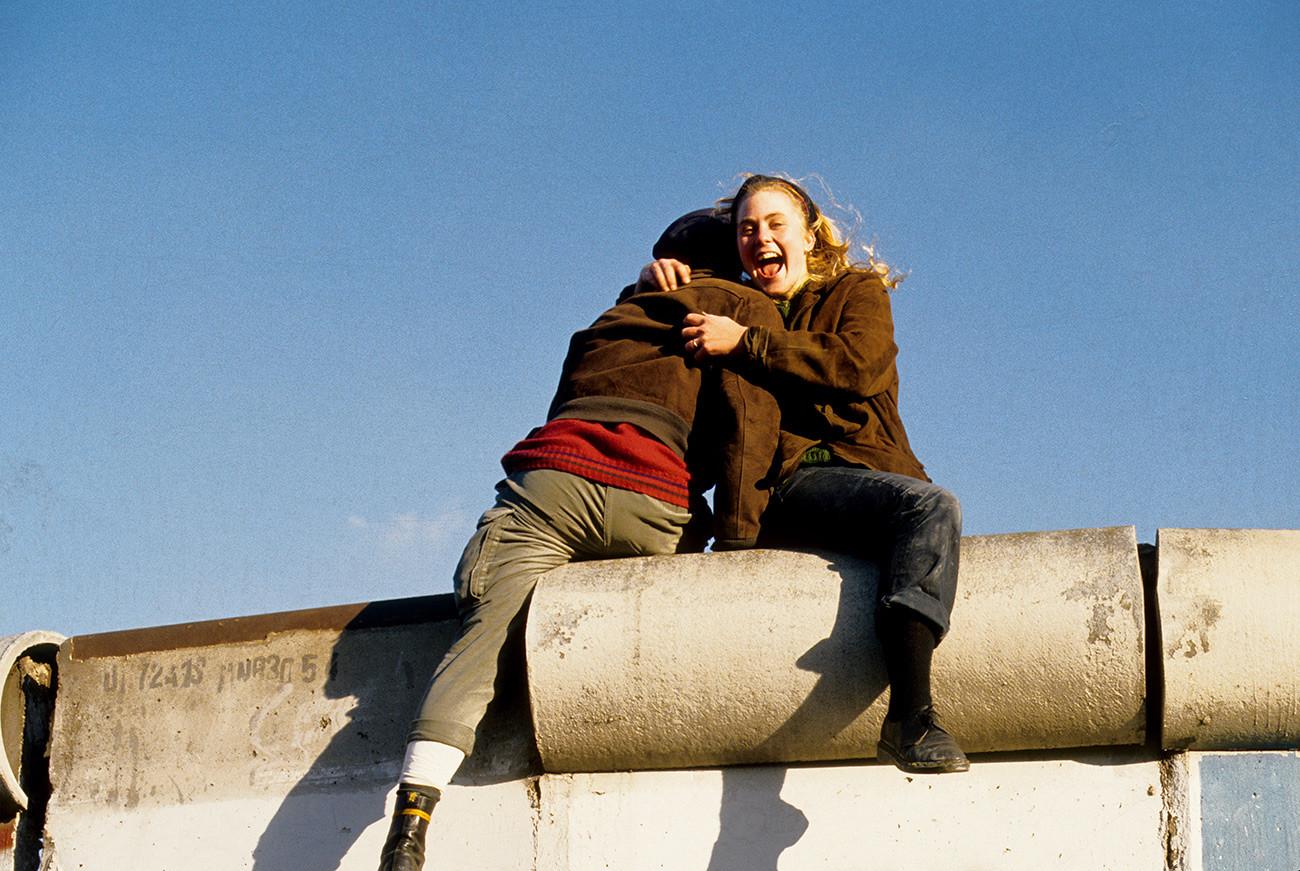 Pasangan kekasih berpelukan di atas Tembok Berlin merayakan keruntuhan tembok itu.