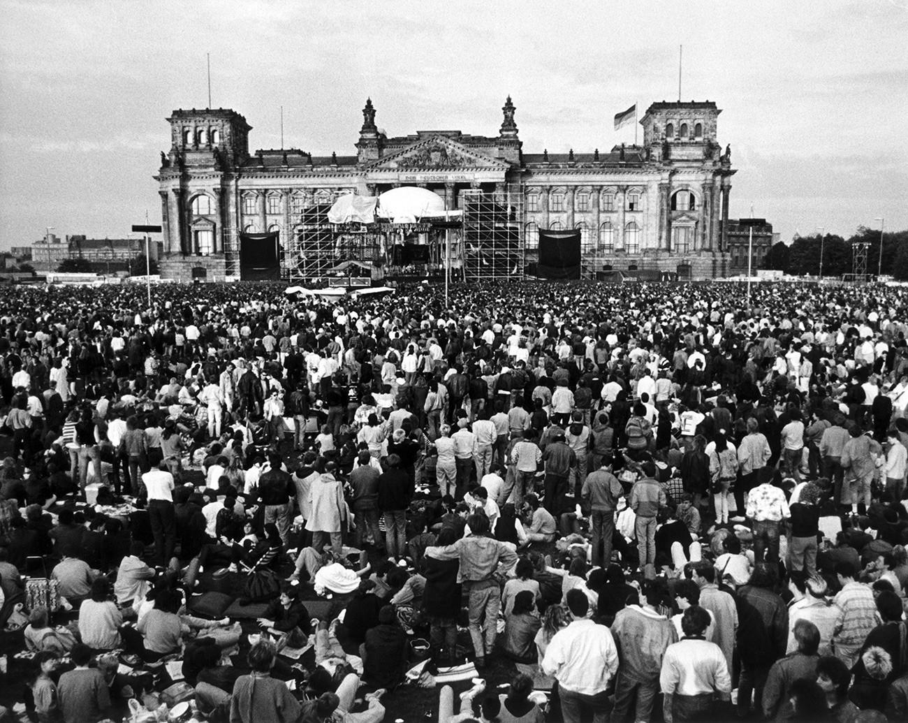 Orang-orang berkumpul saat menonton konser musisi Inggris David Bowie di depan gedung Reichstag, Berlin Barat , 6 Juni 1987.