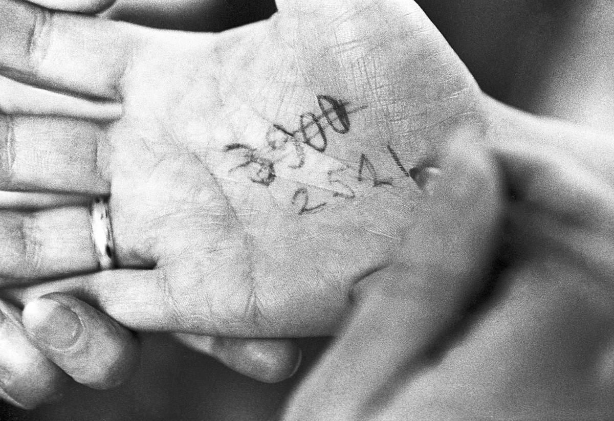 Nomor antrian di telapak tangan seseorang.