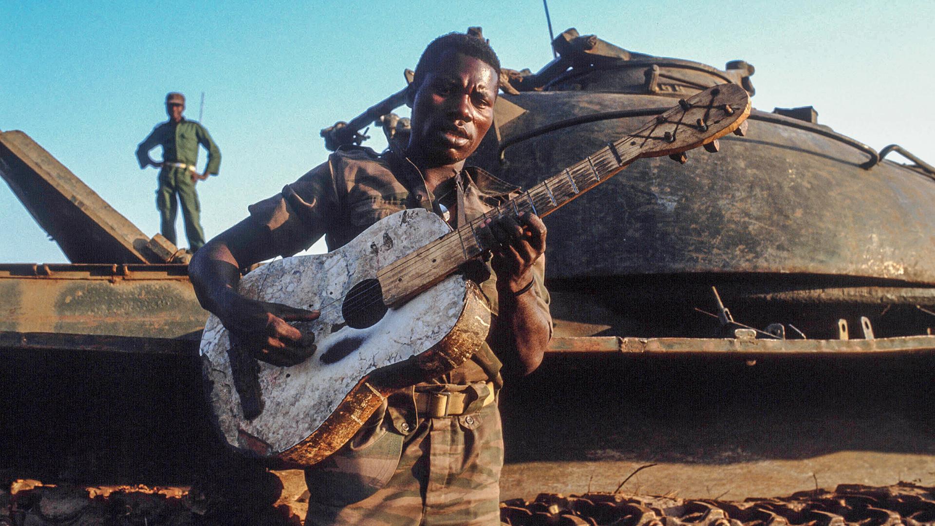 Ein afrikanischer Soldat mit einem sowjetischen Panzer T-34 im Hintergrund