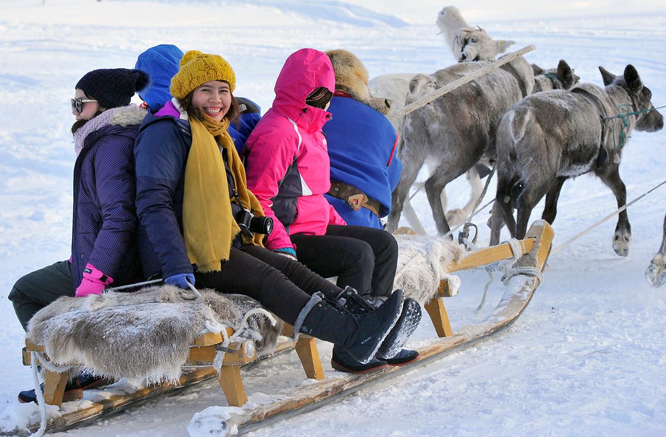 Туристы из Азии во время катания на оленях в Самь Сыйт