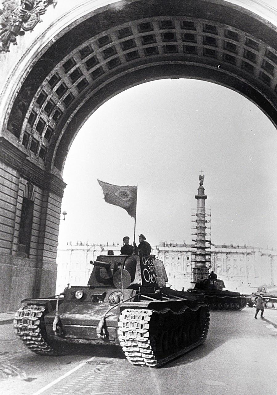 """""""Тенкови тргнуваат на фронт"""". Тенкови КВ-1 составени за време на опсадата на Ленинград во фабриката број 371 тргнуваат на фронт од Урицкиот плоштад (денес Дворцовски плоштад) во Ленинград."""