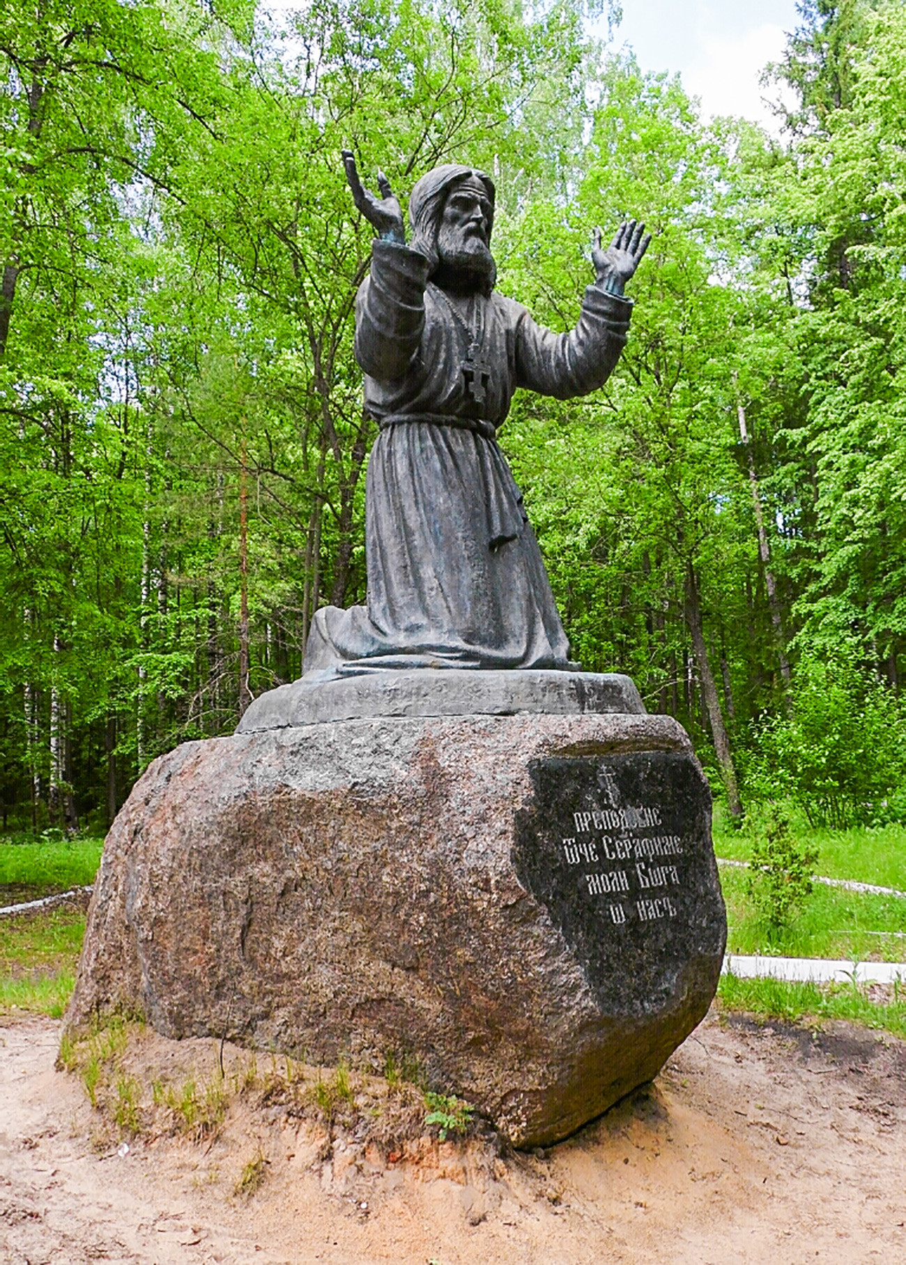 A monument to Saint Seraphim of Sarov standing on a stone