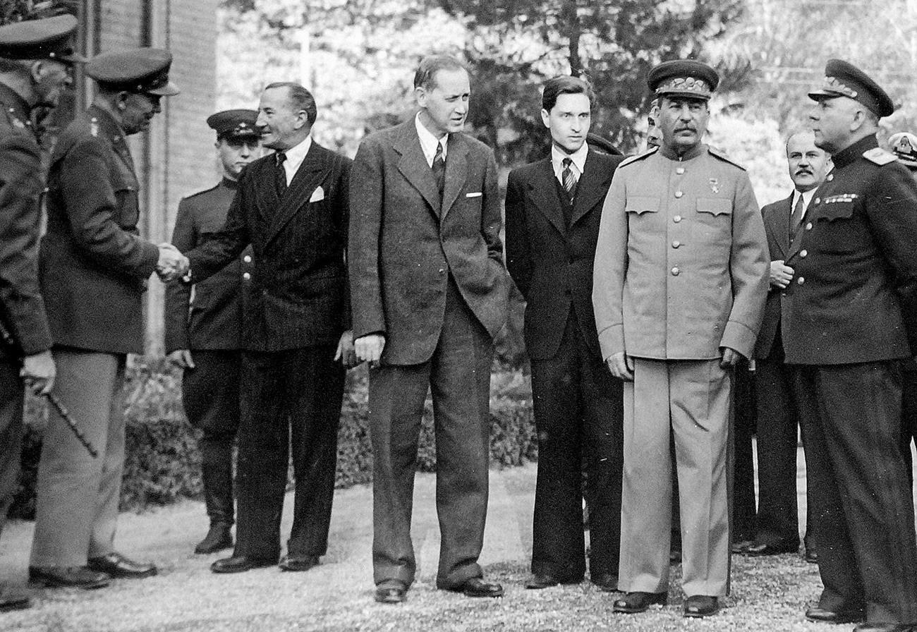 テヘラン会談、1943年11月28日ー12月3日、ロシア大使館の外に立っている(左から)正体不明の英国兵;ジョージ・マーシャルはアルチバルド・ケール英国のソ連大使と握手する;スターリンの通訳者;ハリー・ホプキンス;ヨシフ・スターリン;ソ連の外務大臣ヴャチェスラフ・モロトフ;クリメント・ヴォロシーロフ元帥